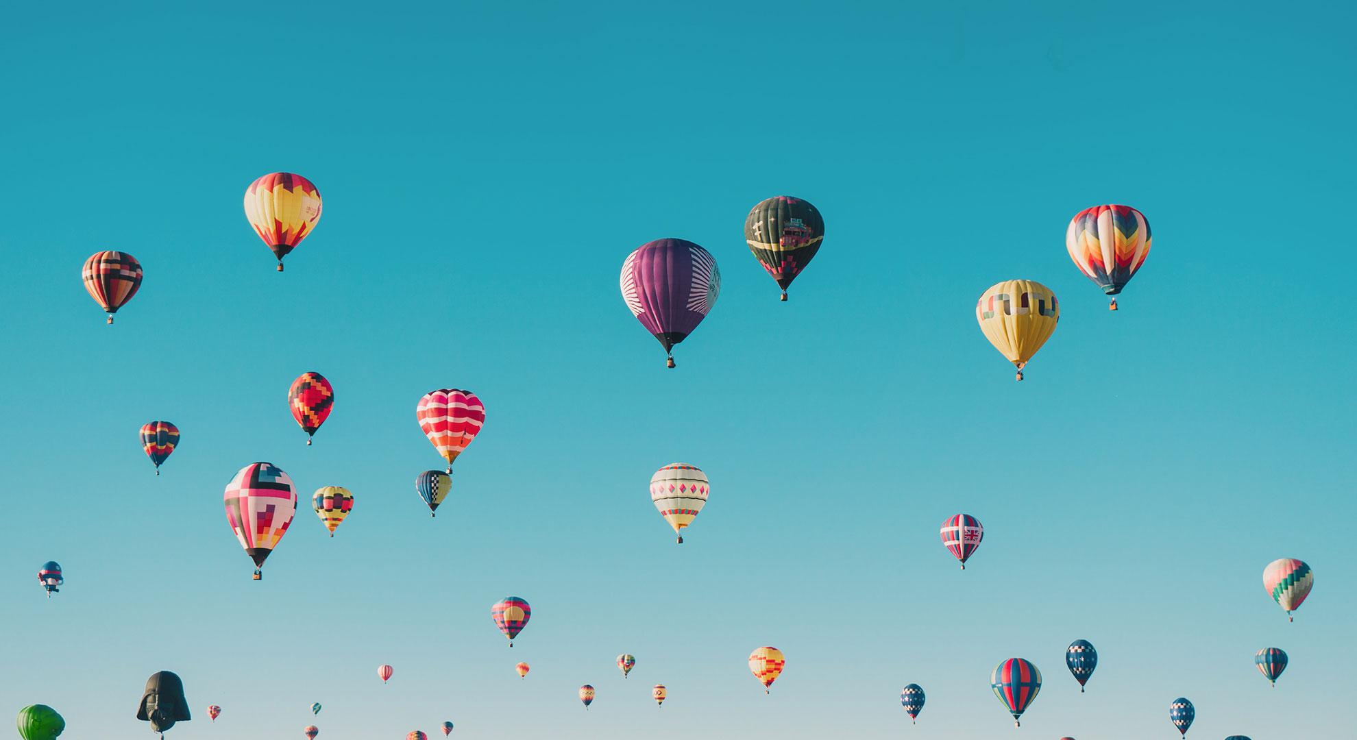 envolée de montgolfières sur fond de ciel bleu flamboyant - header formation intra entreprises kodama